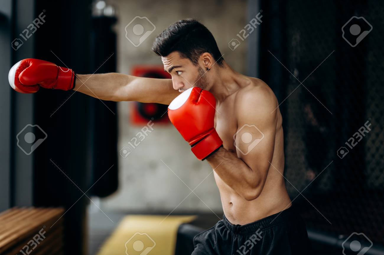 Sportsman with a naked torso and the red boxing gloves on his hands stands  hits with