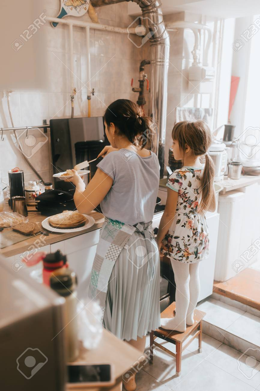 Tremendous Little Girl Staying On The Stool Next To Her Mother Is Cooking Creativecarmelina Interior Chair Design Creativecarmelinacom