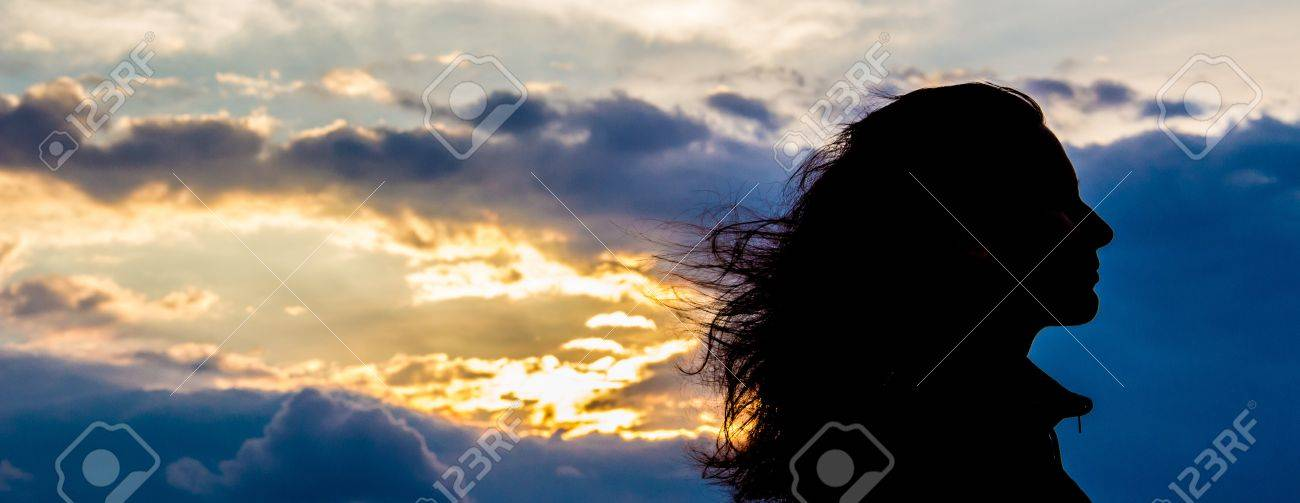 girl silhouette in front of setting sun through blue clouds Stock Photo - 21127441