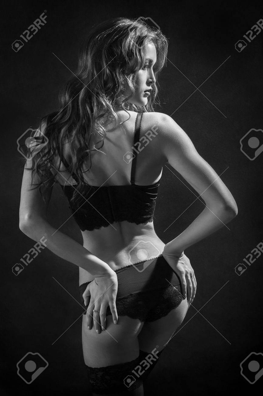 3cc7f35072e8 Mujer bonita en ropa interior y medias muestra su imagen monocroma glúteos