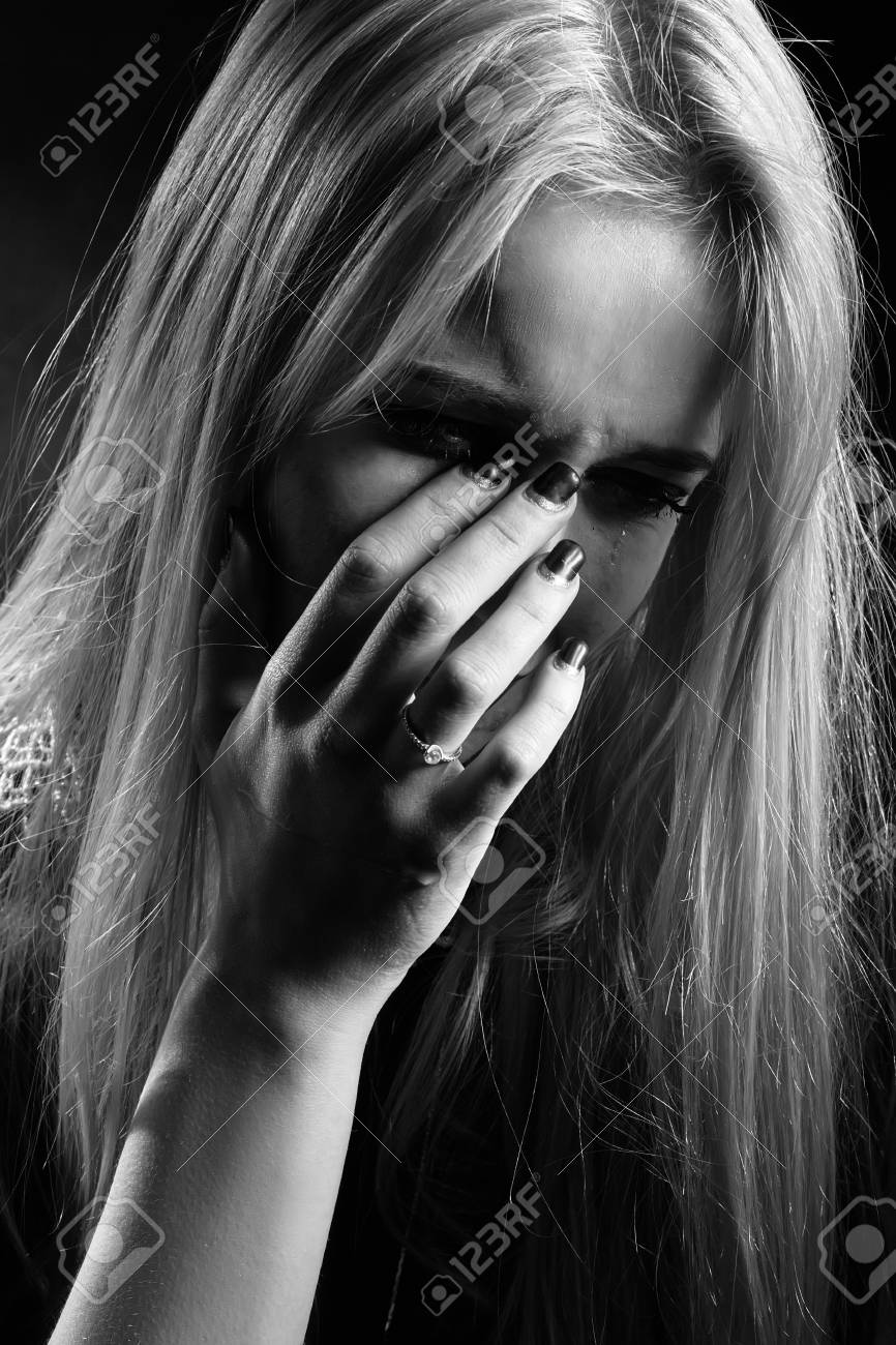 sad girl crying covering her face, monochrome Stock Photo - 63380415