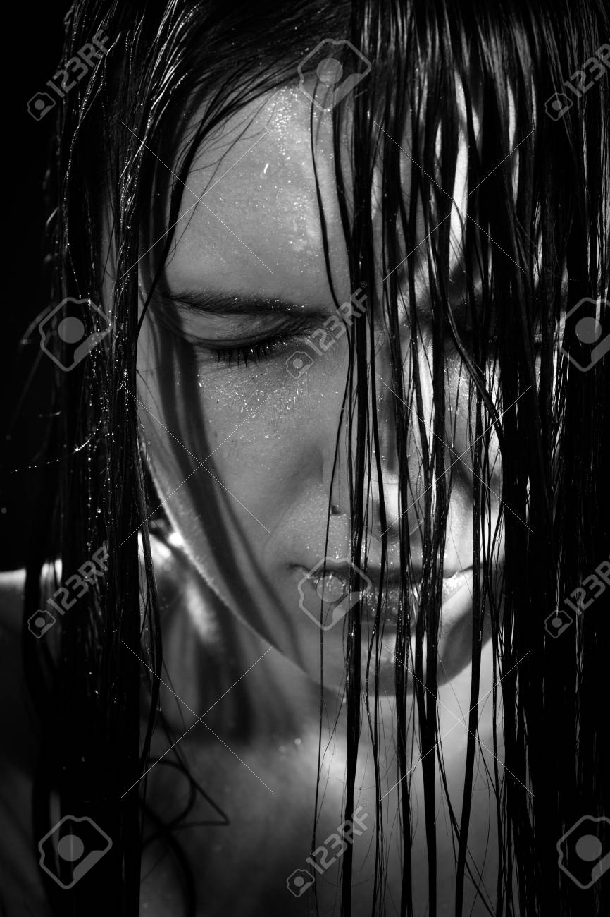 Serious sad woman with wet black hair close her eyes in dark monochrome stock photo