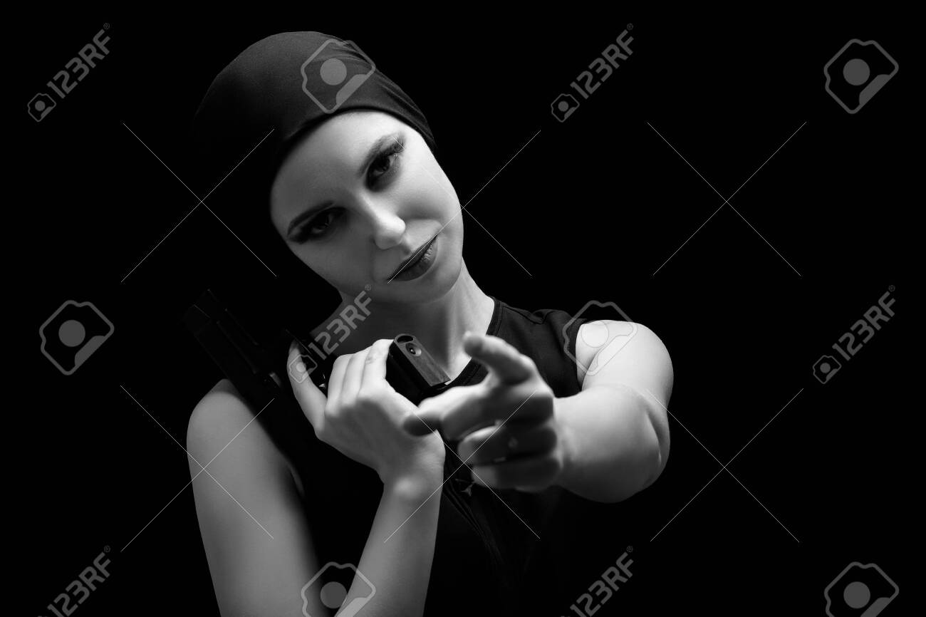 serious girl with gun point at camera on black background, monochrome - 121330464