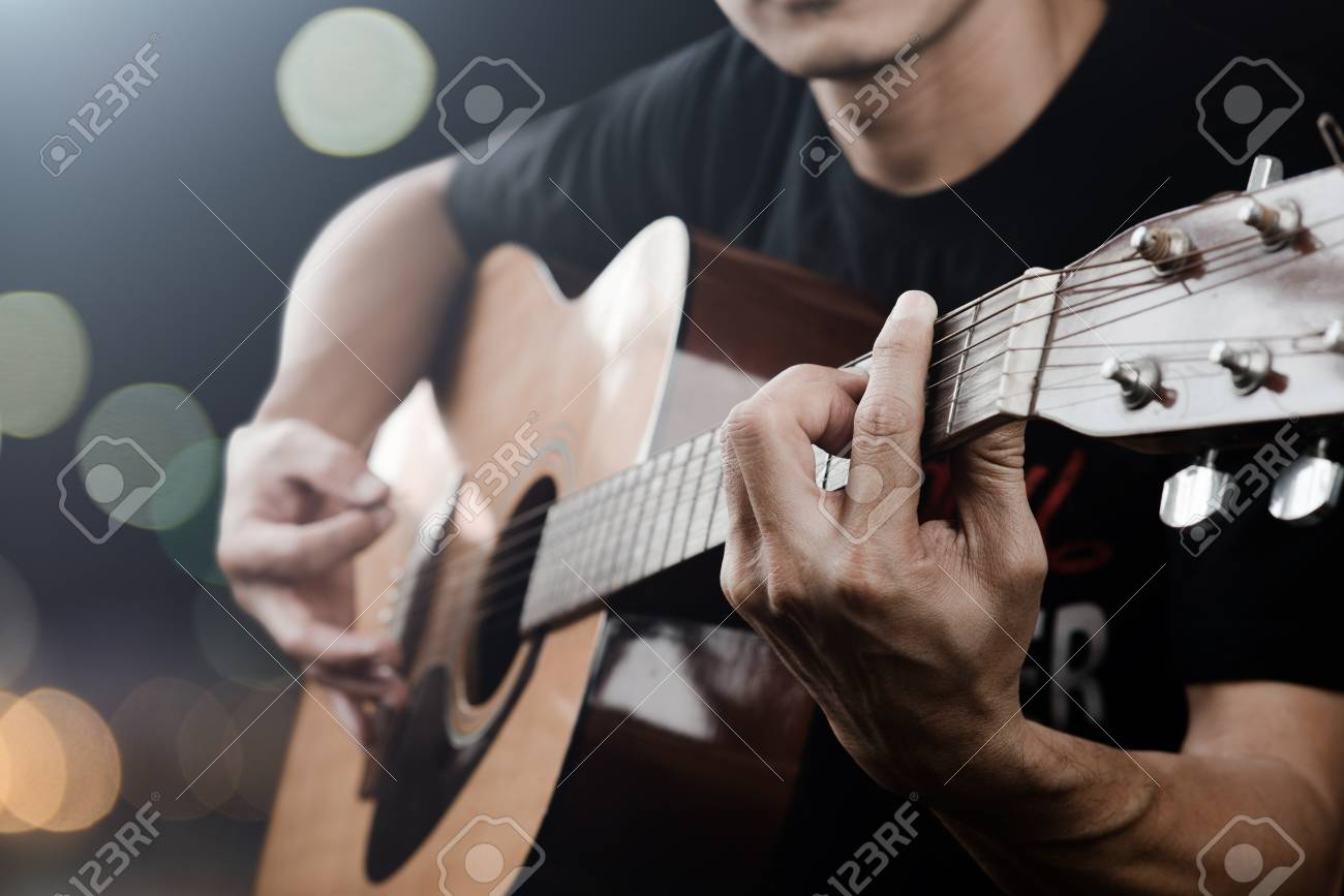 Man Playing Acoustic Guitar With Finger Catching Chord On Bar