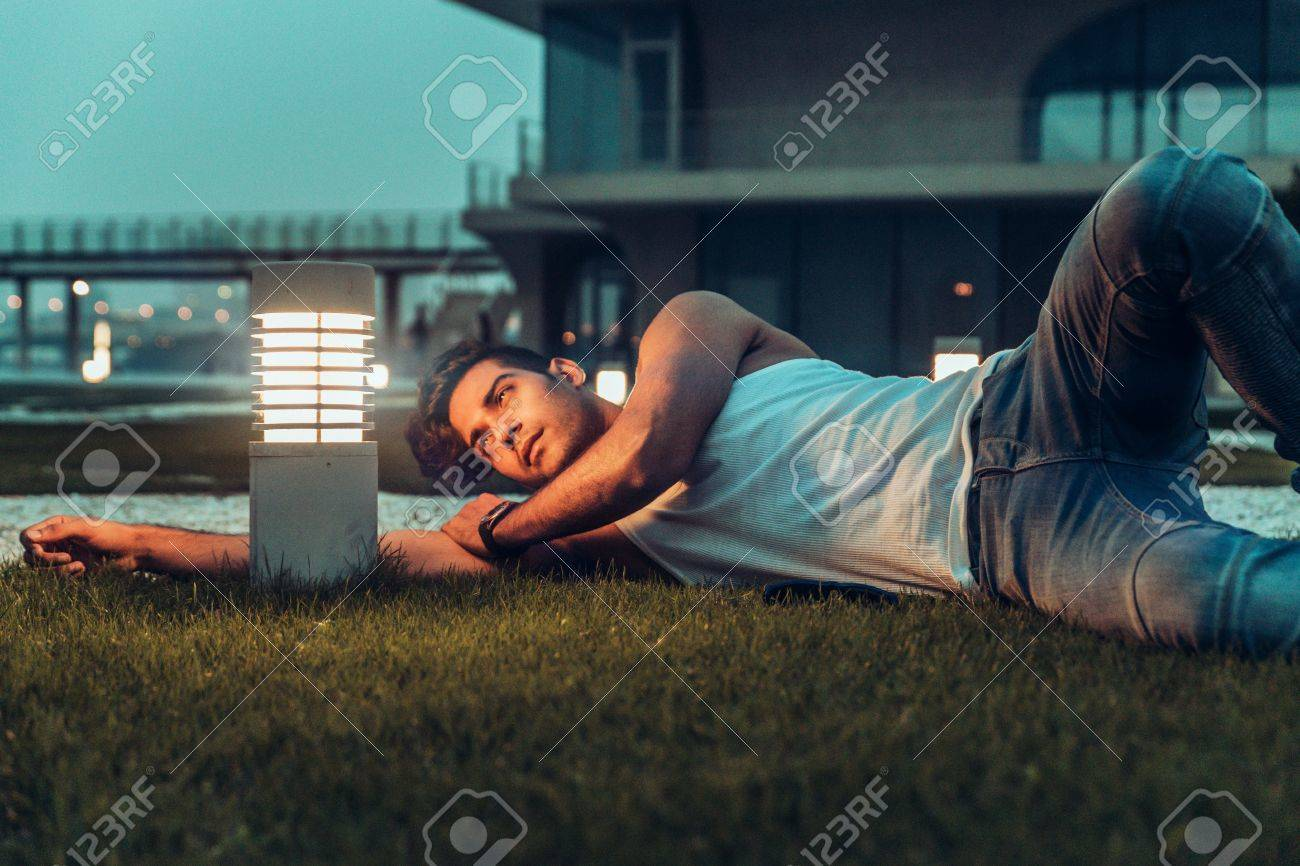 Stock Photo   Stylish Man In The White T Shirt, Leather Jacket And Jeans  Posing Lie On The Floor Near Lamp