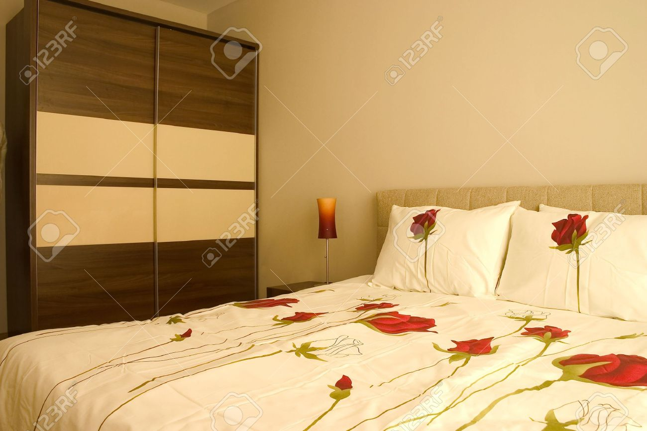 http://previews.123rf.com/images/lemonadv/lemonadv0907/lemonadv090700018/5247574-Warm-camera-da-letto-con-armadio-e-letto-matrimoniale-con-cuscini-e-lenzuola-rose--Archivio-Fotografico.jpg