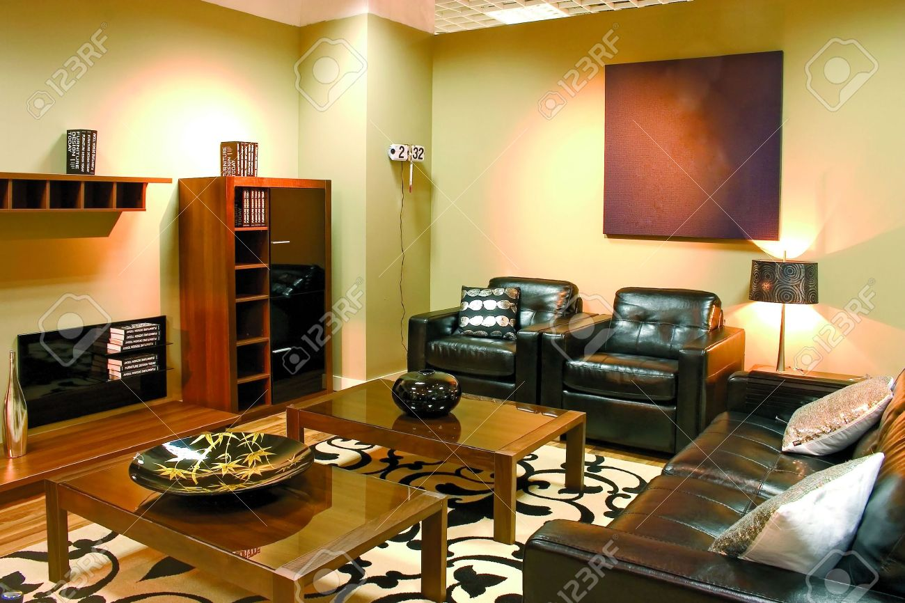 Modern living room with warm colors. Leather sofa, two arm-chairs..