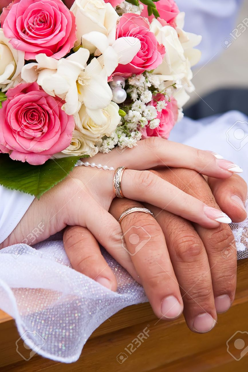Hands of bride and groom and rings with wedding bouquet Stock Photo - 10272086