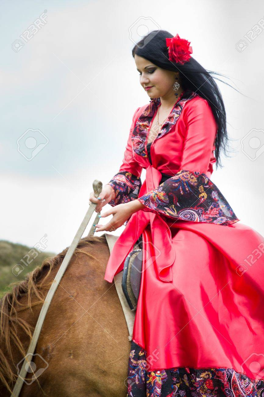 Beautiful gypsy girl riding a horse in the field Stock Photo - 10448416