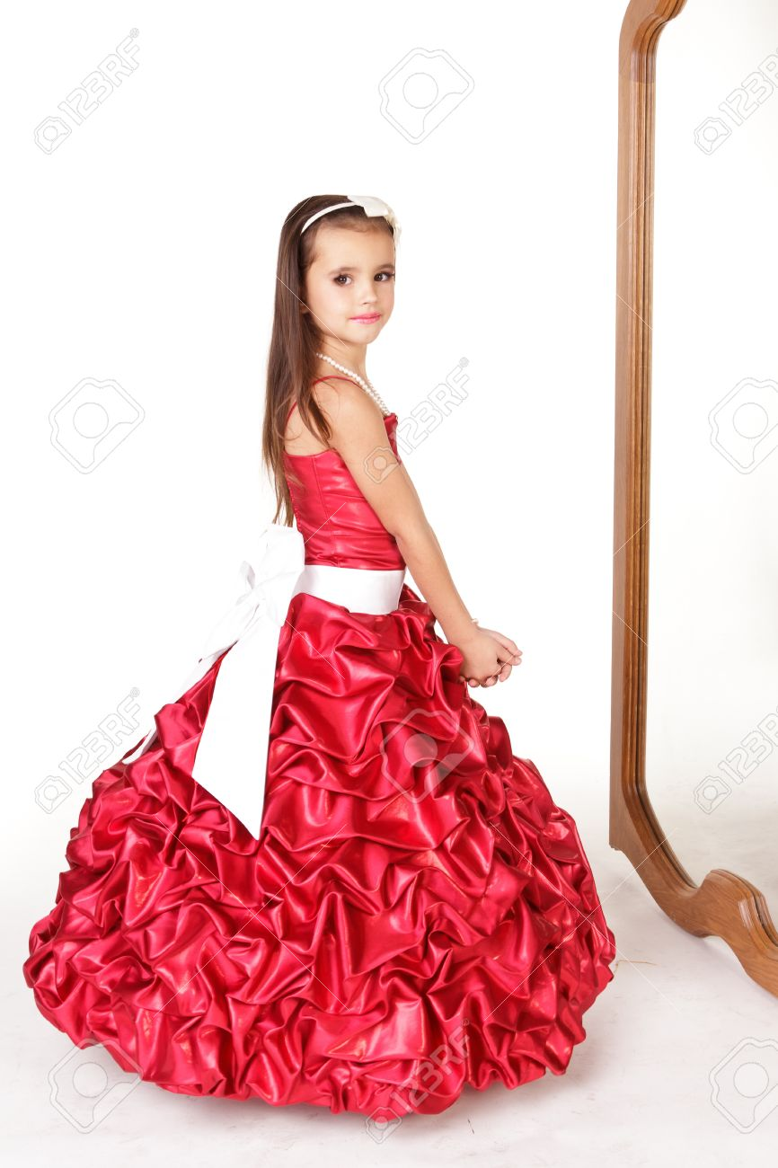 031b1968ea74 Beautiful little girl in red evening dress in front of mirror on white  background Stock Photo