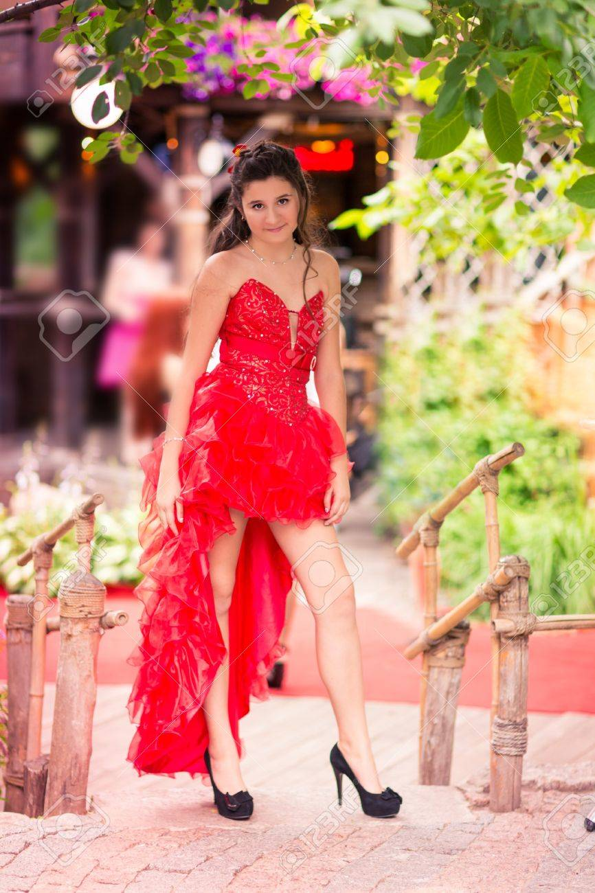 Beautiful girl in a gorgeous red dress in a park outdoor - 20538289