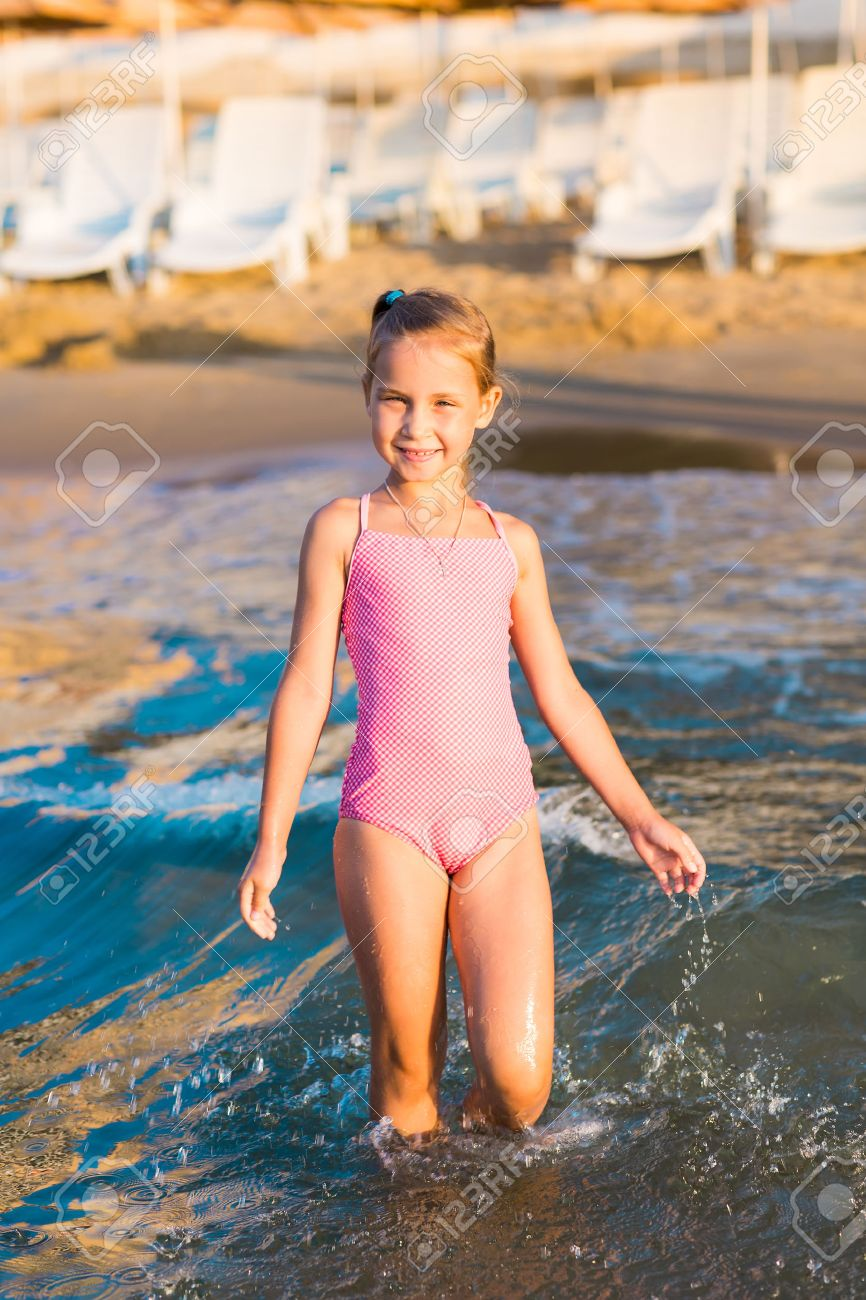 Adorable happy little girl playing in the sea on a beach.