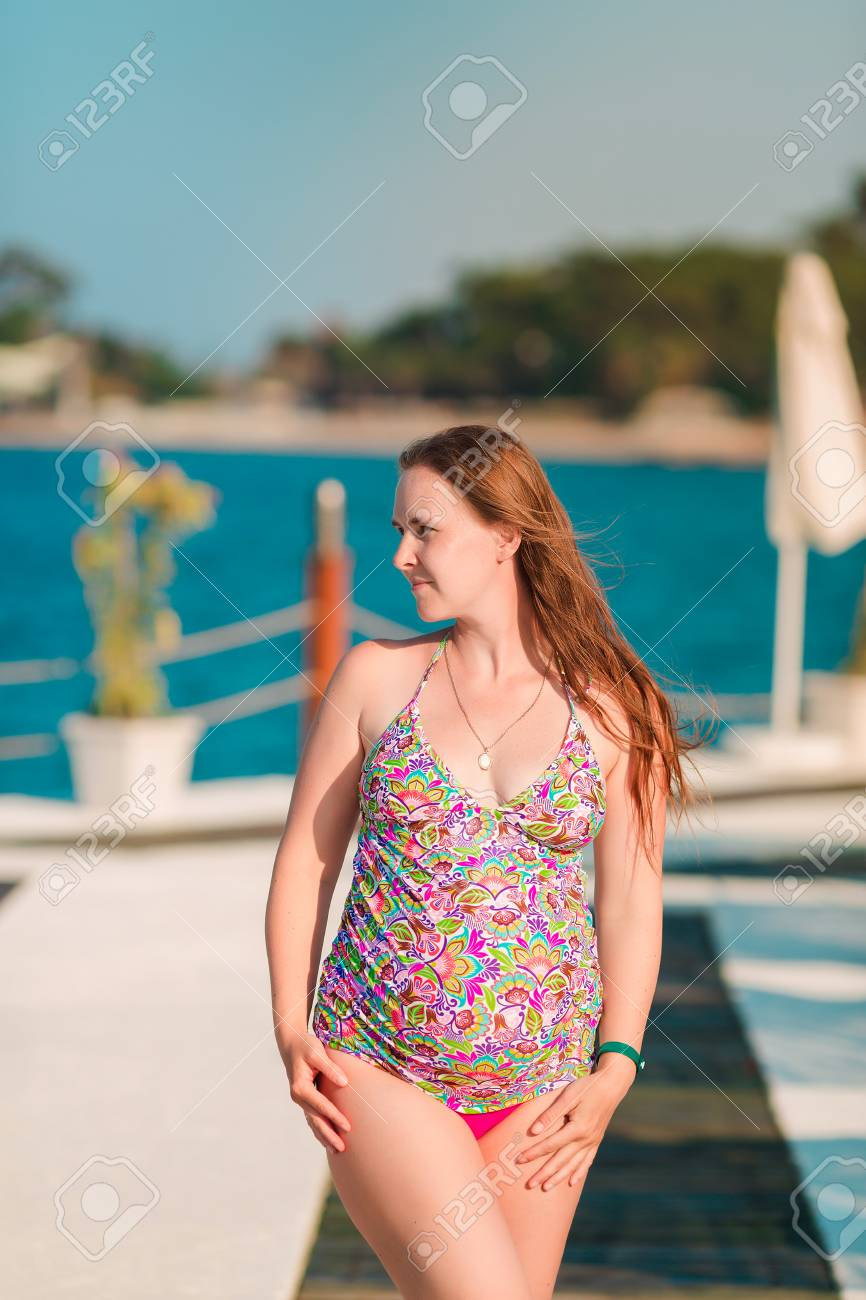 685ca95581bc5 Beautiful pregnant woman relaxing in swimming-suit at the beach. Enjoying  pregnancy concept.