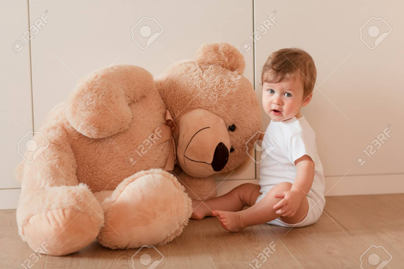 Cute Little Baby Boy With Big Teddy Bear Sitting In The Room Stock