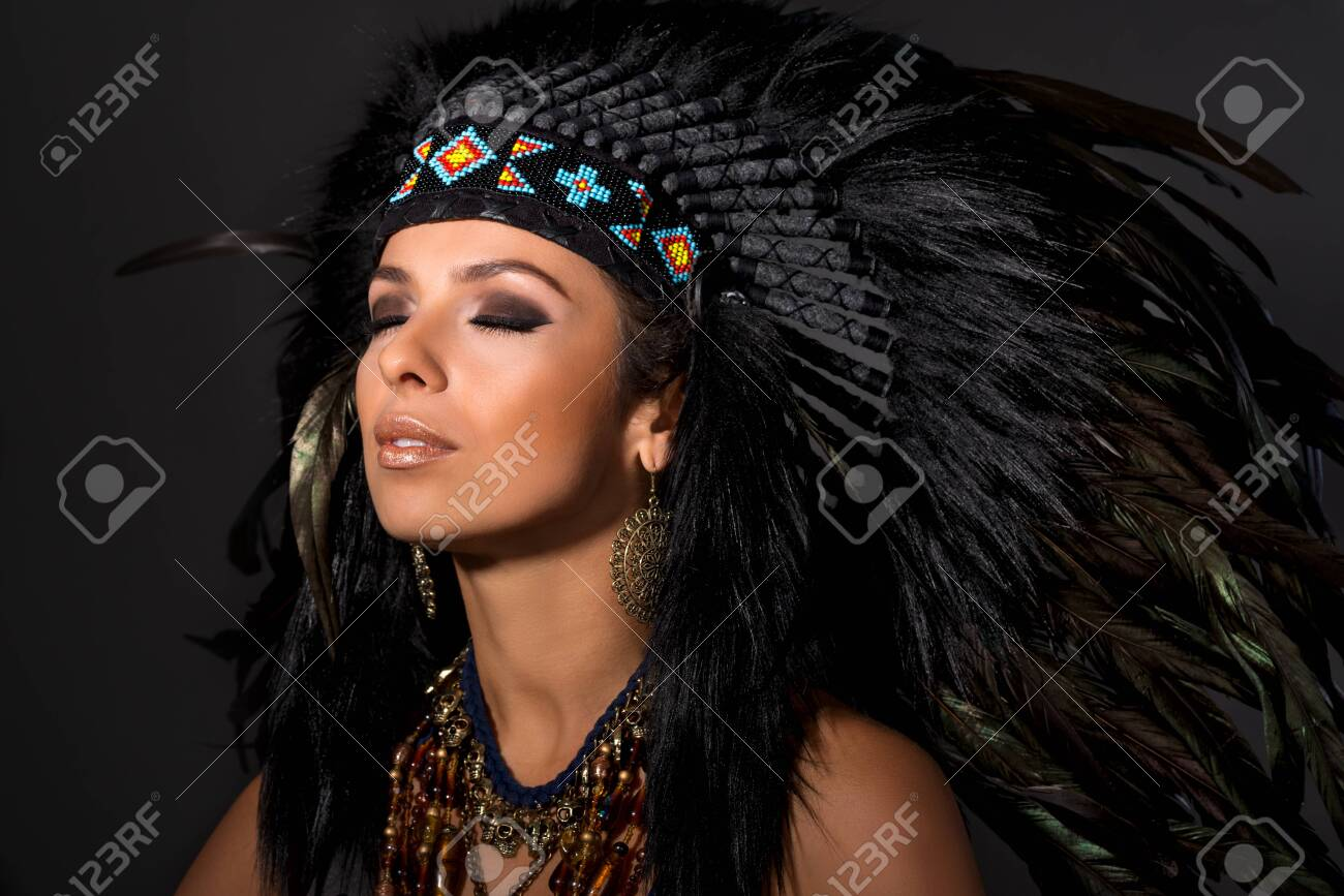 Portrait of young beautiful woman in costume of American Indian with closed eyes.Studio shot. - 131956139