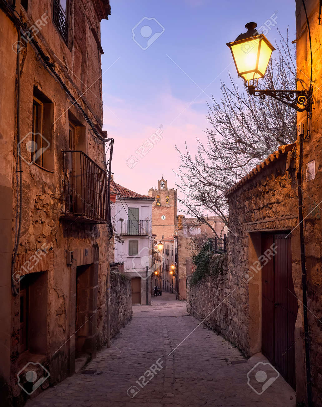 Historic architecture of the streets and tower of the Romanesque cathedral of the city of Siguenza, Guadalajara, Spain, at sunset - 157602571