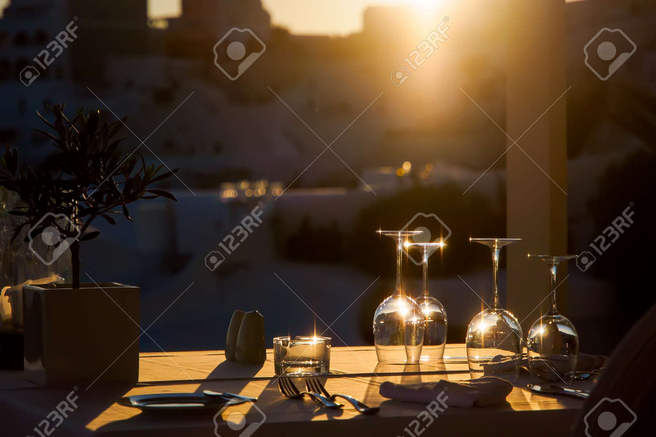 Restaurant table decorated with glasses on terrace in sunset light on the island Santorini, Cyclades, Greece - 148249432