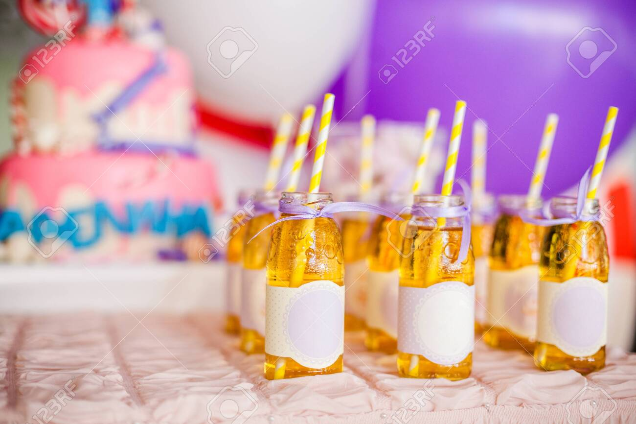 Birthday party concept, candy bar for children. A lot of bottles of apple juice, white and yellow straws, big pink cake and white and purple ballons on background - 120314760