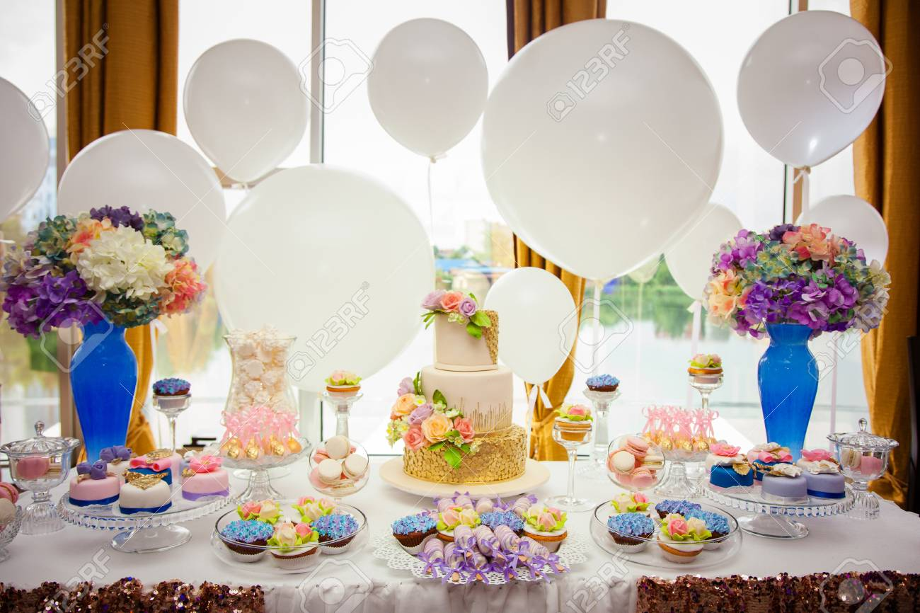 Candy bar on golden wedding party with a lot of different candies, cupcakes, souffle and cakes. Decorated in brown and purple colors, nature and eco theme, indoor. - 120314888