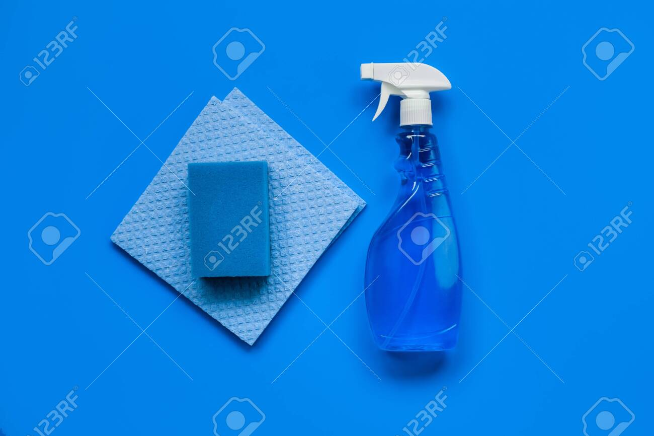 Transparent blue sprayer with window cleaner, rags and sponge on blue background. The view from the top. - 120886337