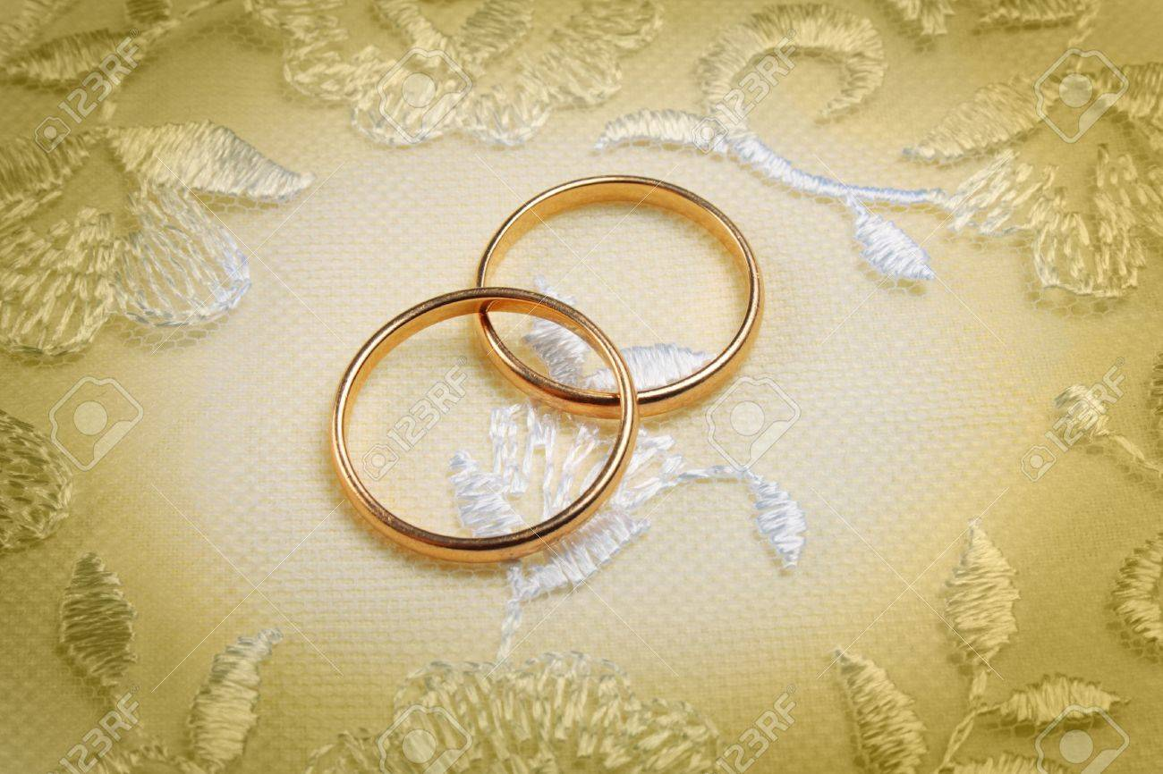 pair of golden wedding rings over invitation card decorated with lace stock photo 12121342
