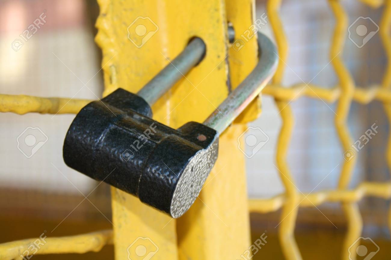 brass padlock and chain on yellow cell door Stock Photo - 13401191