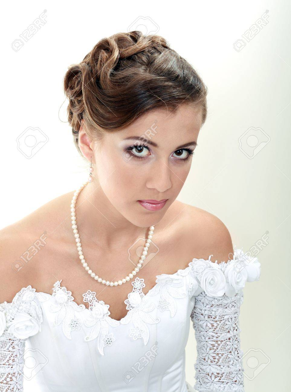 Beautiful young woman in white dress and pearl necklace beige background Stock Photo - 13876513