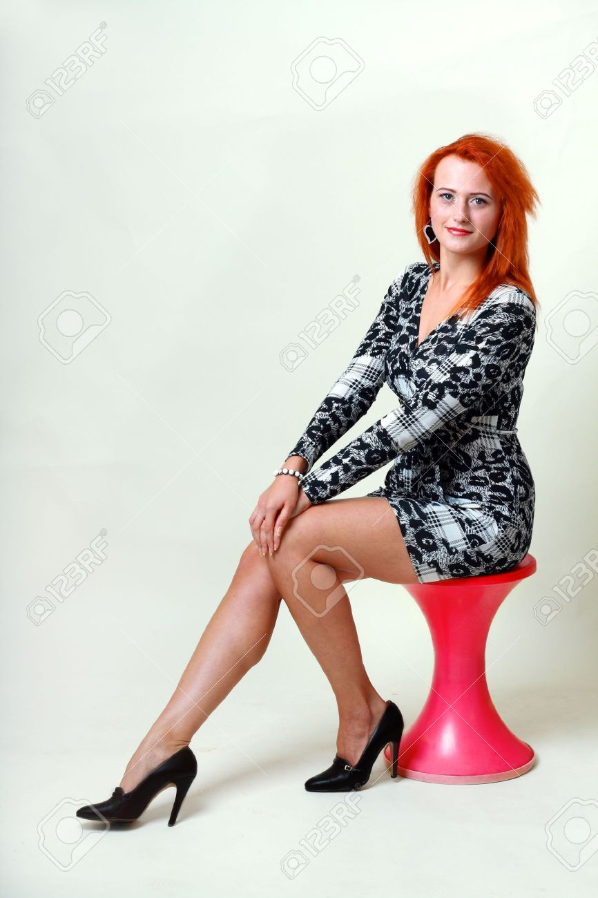Young lady in dress sitting on red chair on light grey background Stock Photo - 15037482
