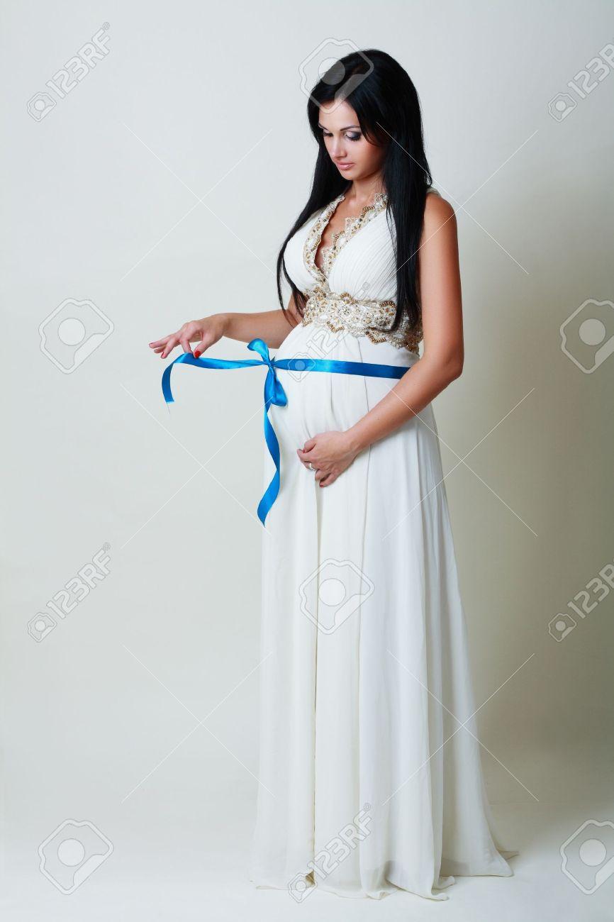 d7065e052e02 Banque d images - Belle femme enceinte en robe blanche longue avec un ruban  bleu attaché