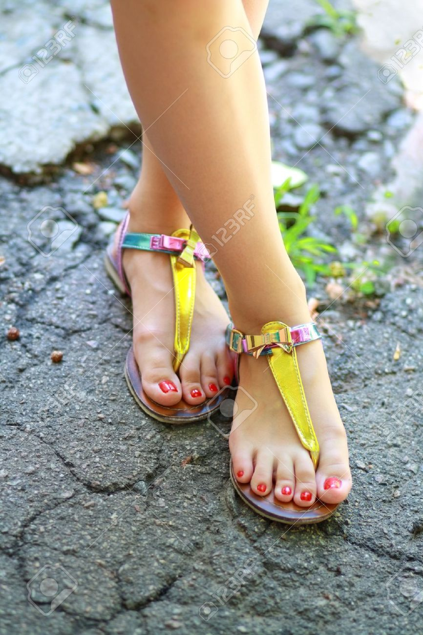 516f669585c46 Stock Photo - Young girl s feet wearing summer sandals and standing on old  asphalt road.