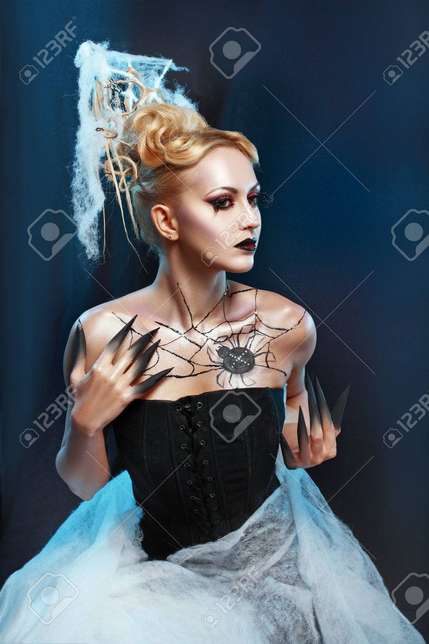 beautiful woman in halloween costume with spider on web bodyart acting as spider queen stock photo