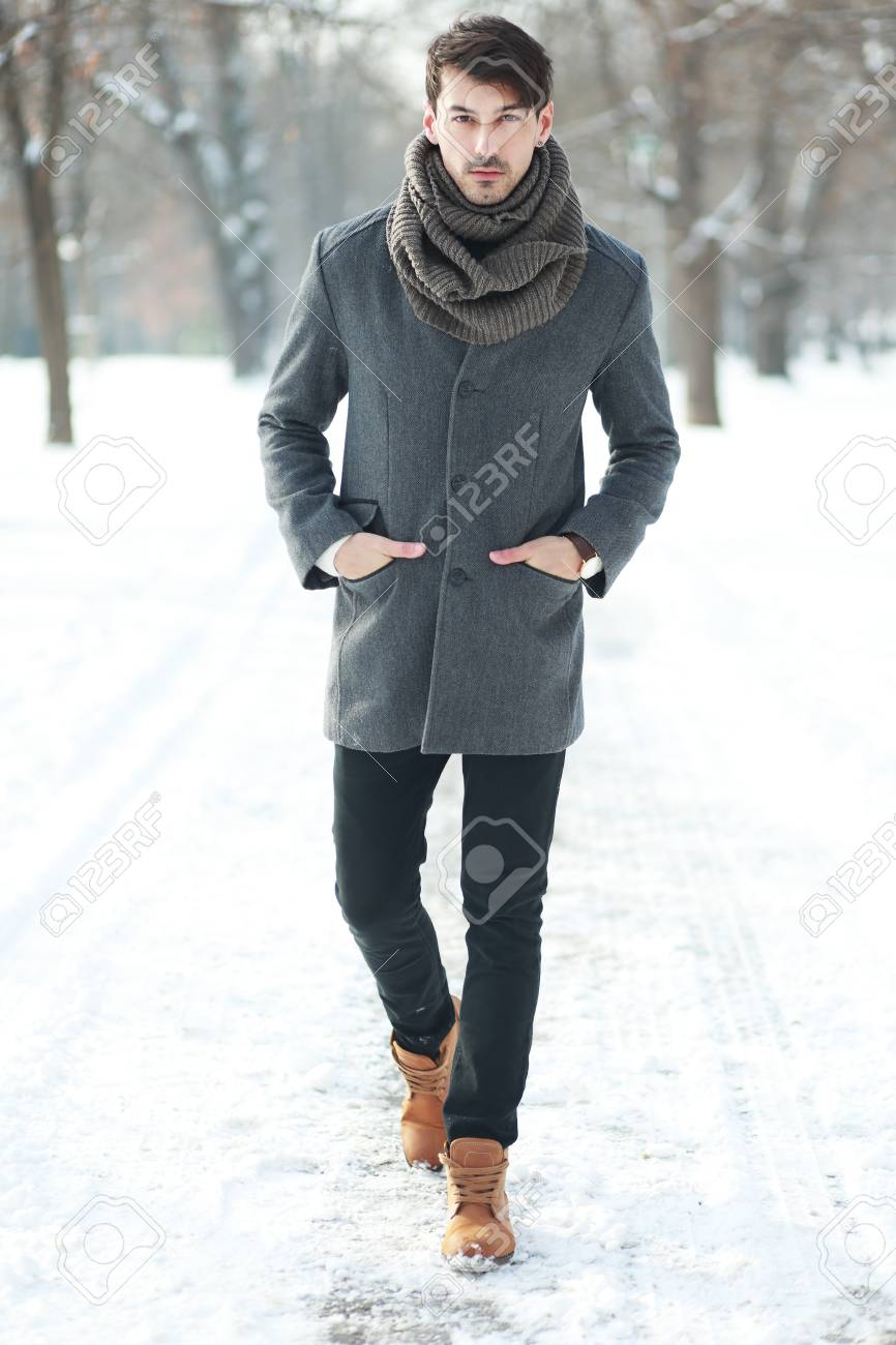 Outdoor portrait of smiling handsome man in coat and scurf. Casual..