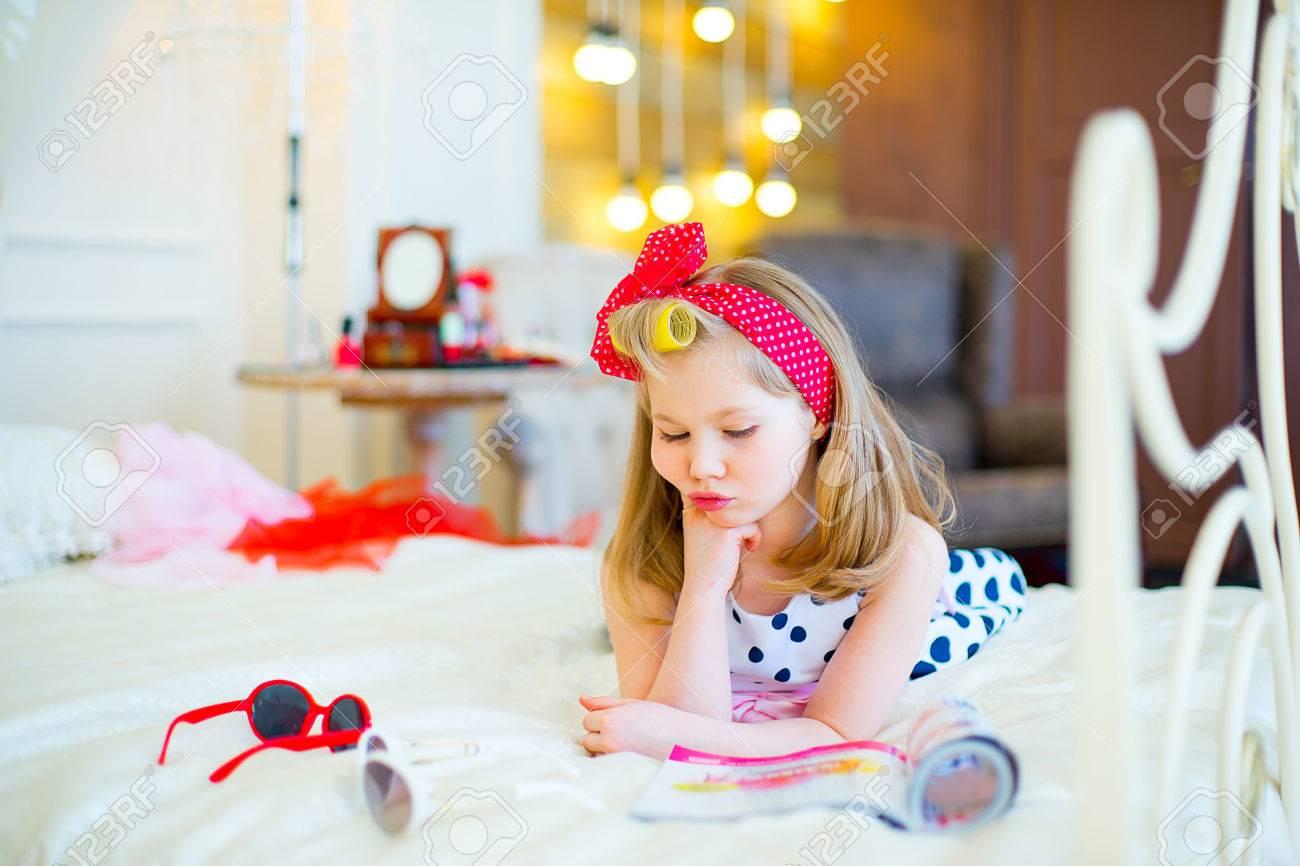 La bambina pone in stile pin up su un letto con gli occhiali da ...