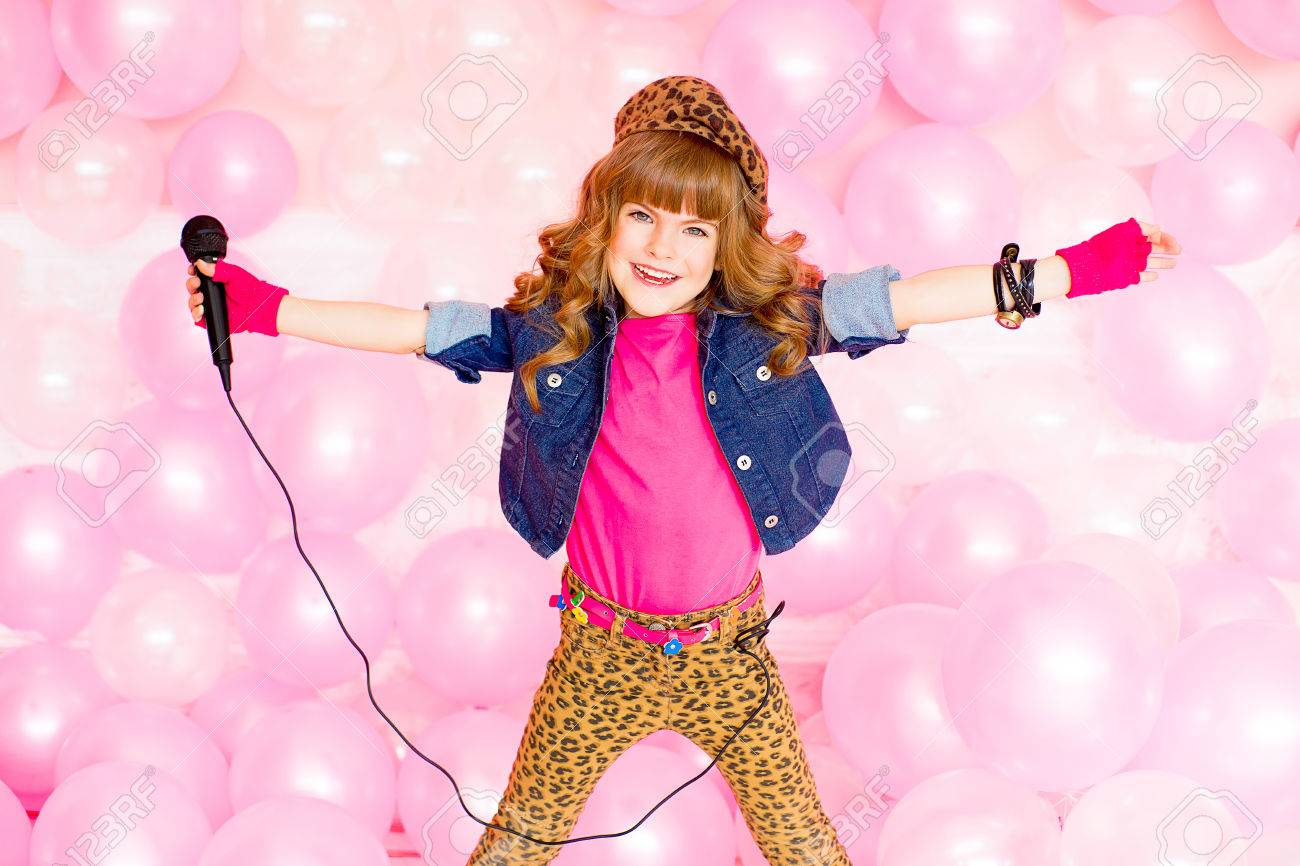 Stock Photo Little Girl Singing A Song With A Microphone On A Background Of  Pink Balloons