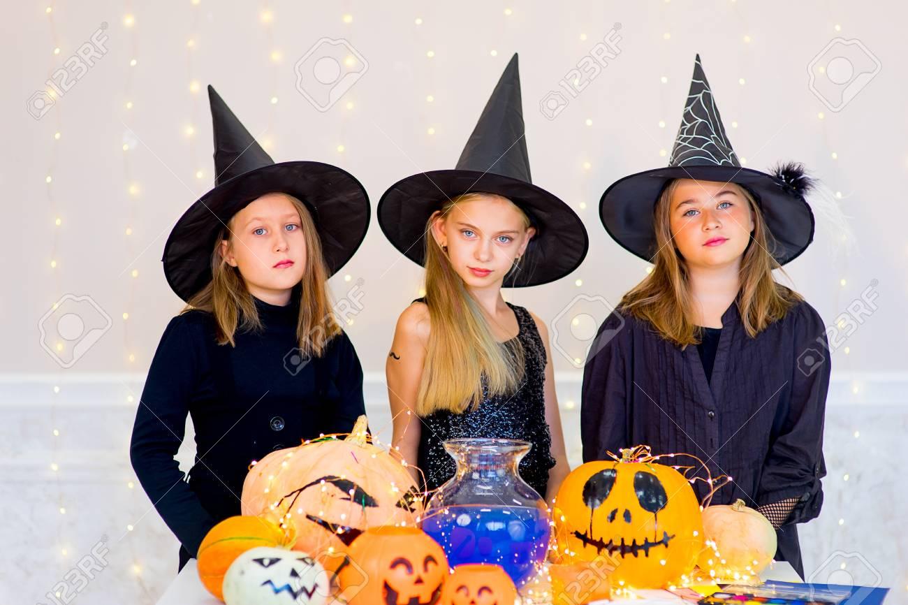 Halloween Gruppo.Felice Gruppo Di Adolescenti In Costume Durante La Festa Di Halloween Giocando Intorno Al Tavolo Con Zucche E Bottiglia Di Pozione