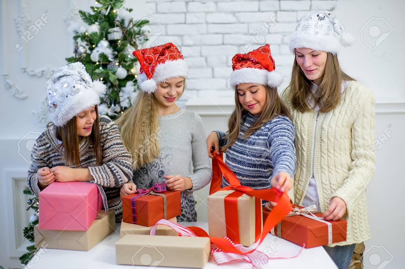 Mädchen Weihnachtsgeschenke roten Band verpackt stehen um den Tisch