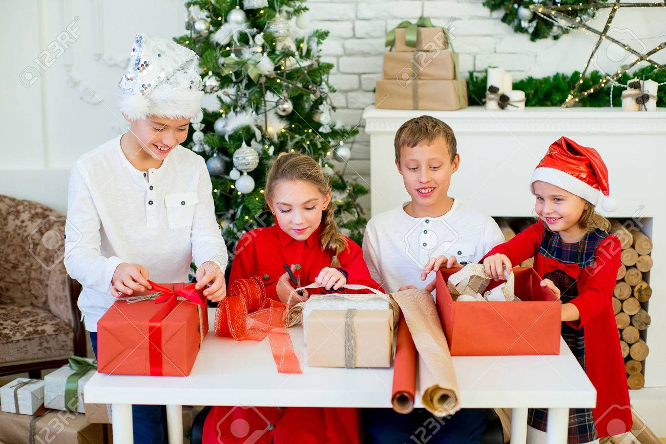Group Of Kids Preparing Gifts For Christmas At Home, Cozy Holiday ...