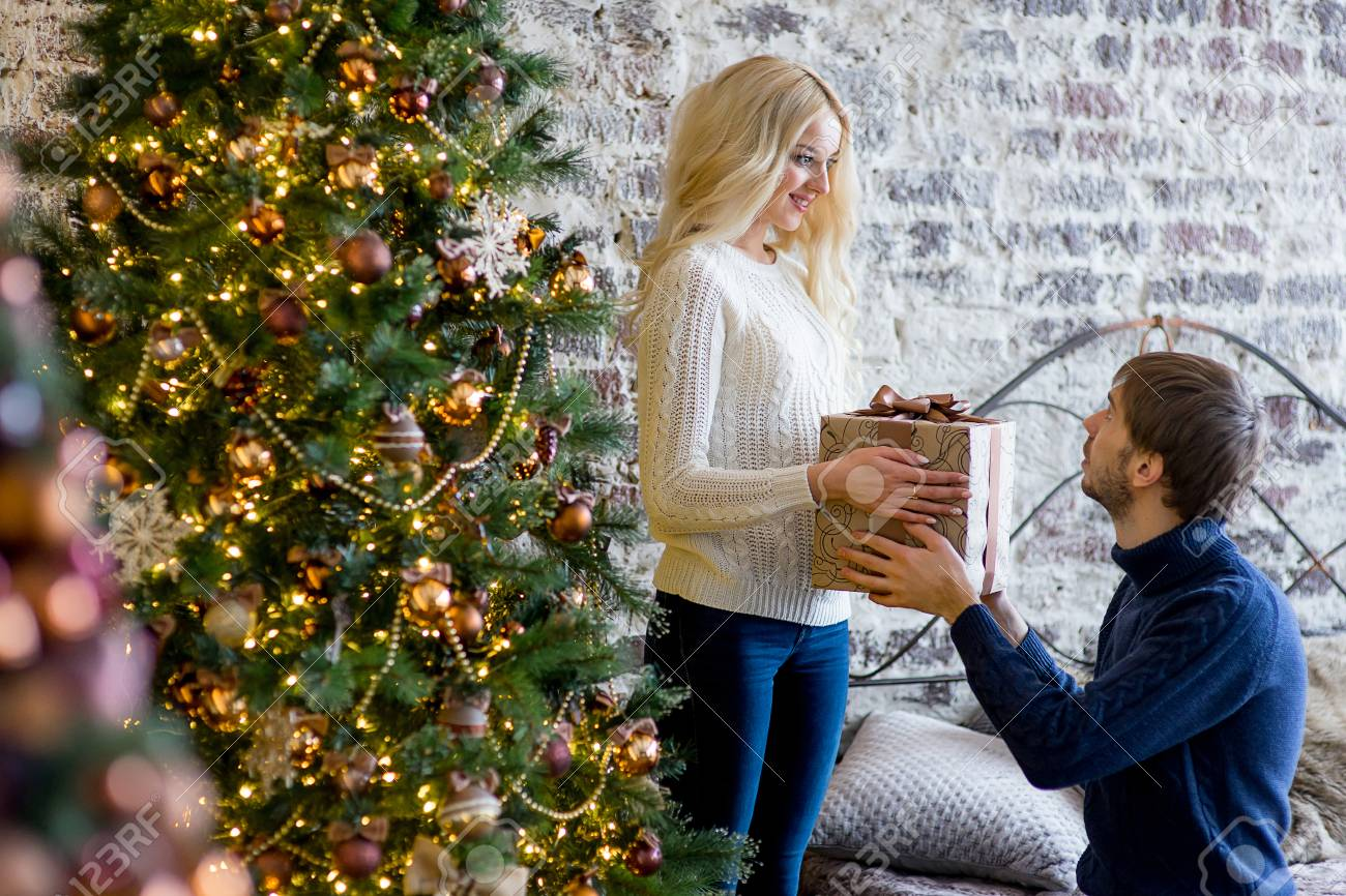 Mann, Der Dem Mädchen Ein Geschenk Macht, Während Sie Weihnachtsbaum ...