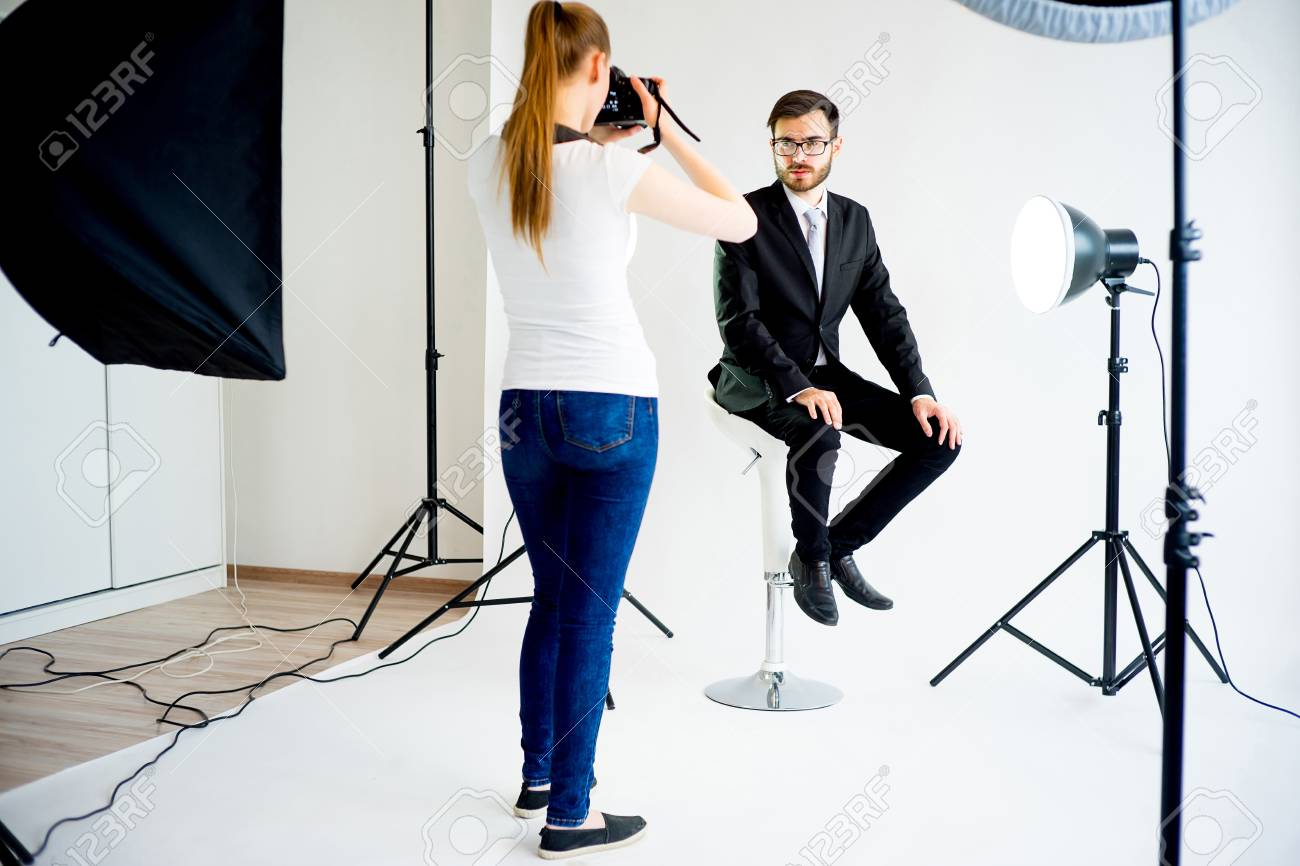 Female Photographer Taking Picture Of A Male Model In Studio Stock Photo