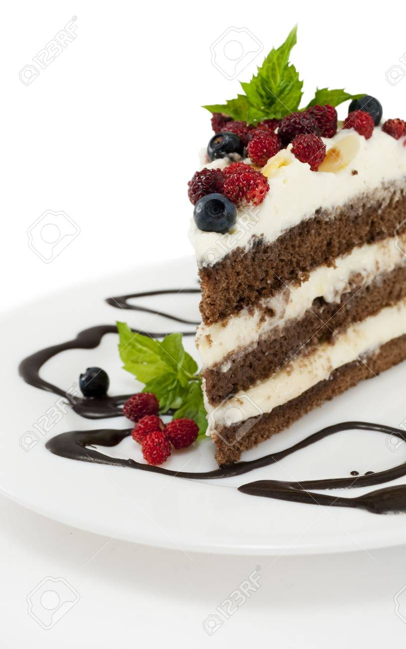 Piece of chocolate cake with chocolate glaze, whipped cream, wild strawberry and  blueberries on white isolated background Stock Photo - 14855429