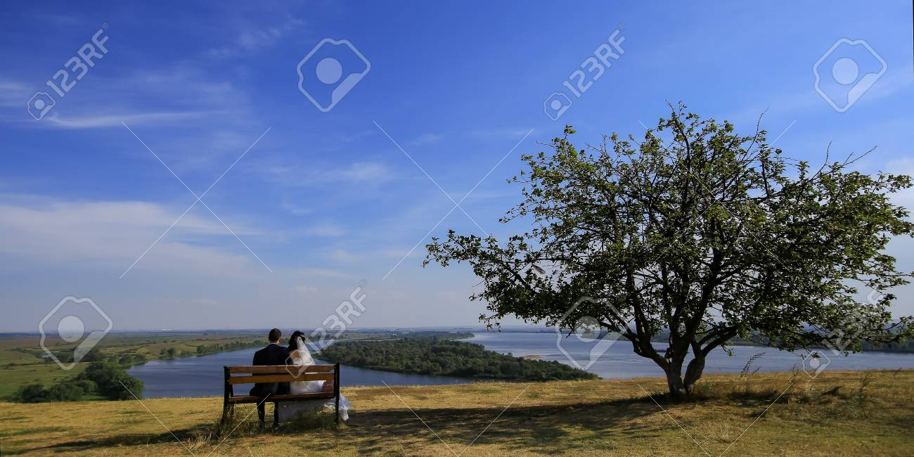 Brilliant Young Wedding Romantic Couple Sitting On Wooden Bench Outdoor Ocoug Best Dining Table And Chair Ideas Images Ocougorg