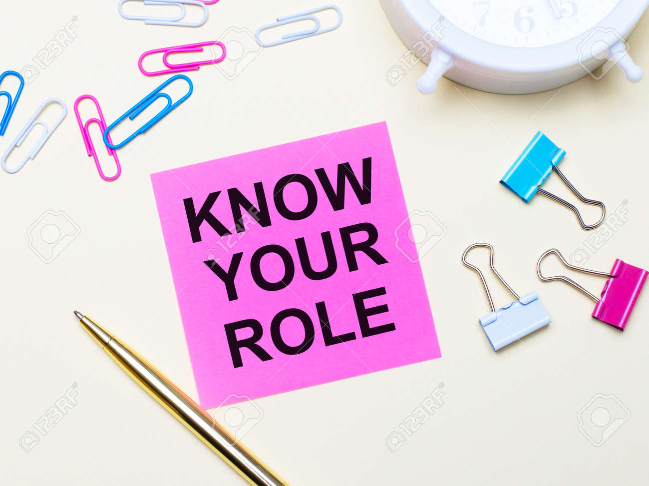 On a light background, a white alarm clock, pink, blue and white paper clips, a golden pen and a pink sticker with the text KNOW YOUR ROLE - 172494897
