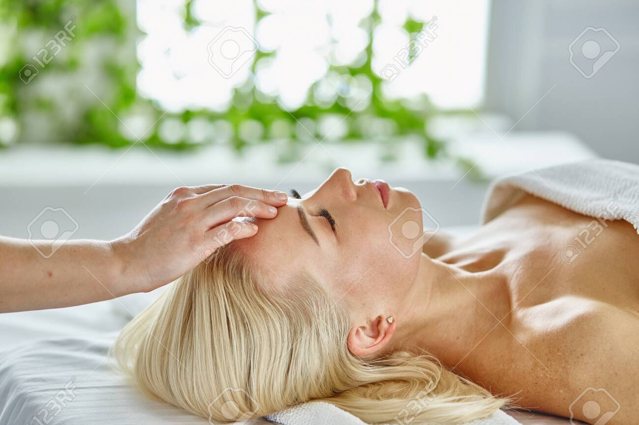 Beautiful woman with closed eyes getting a massage in the spa salon. - 141620817