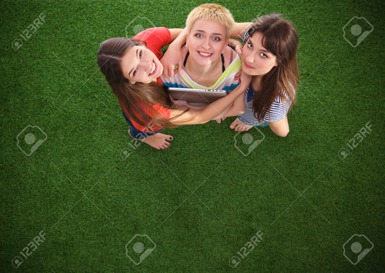three women with naked feet standing in grass holding laptop stock