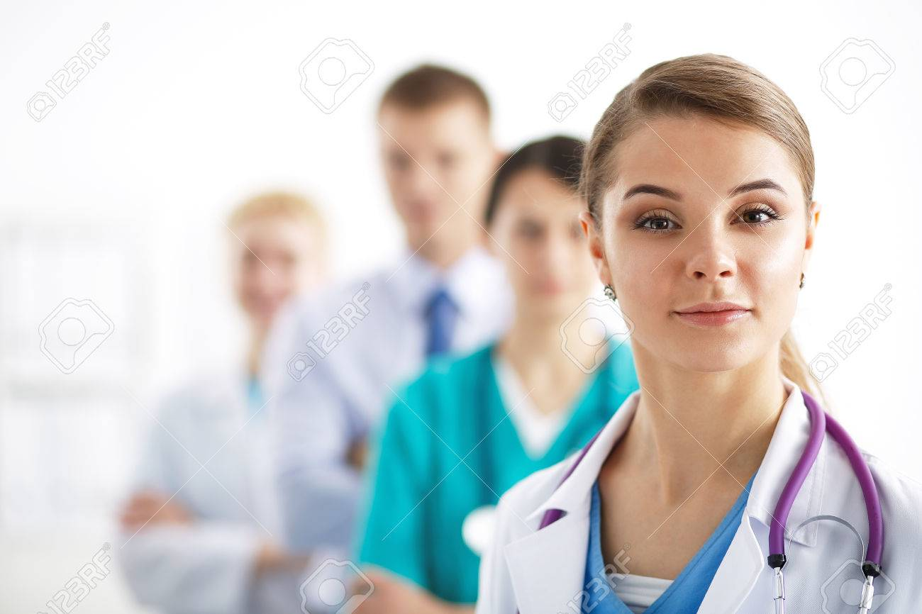 Attractive female doctor in front of medical group . - 43526857