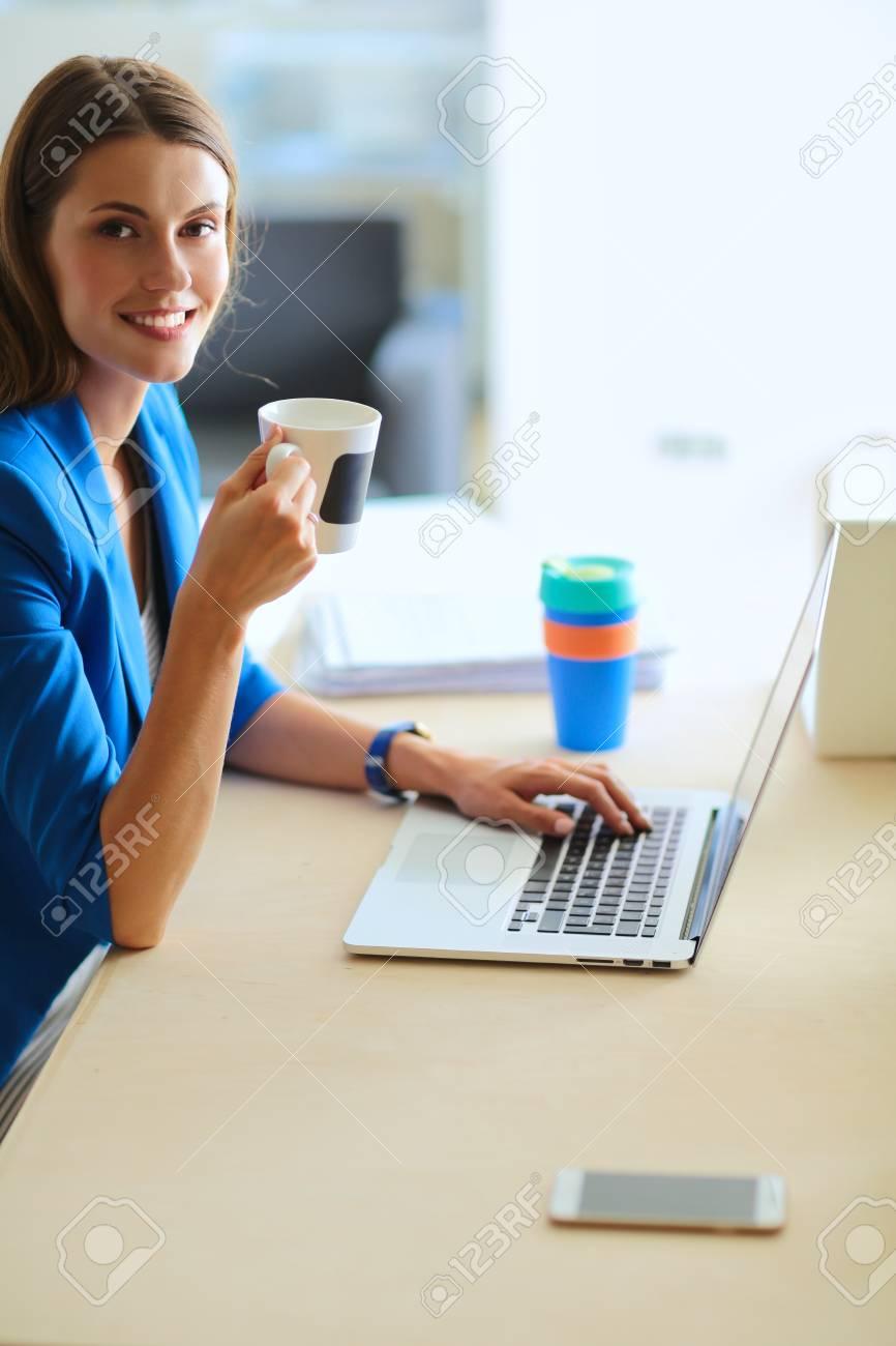 Attraente donna d'affari seduto alla scrivania in ufficio, con una tazza di caffè
