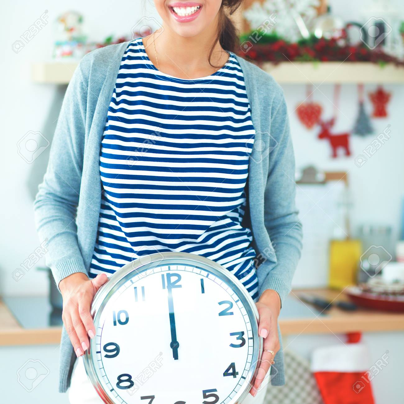 Happy Young Woman Showing Clock In Christmas Decorated Kitchen Stock ...