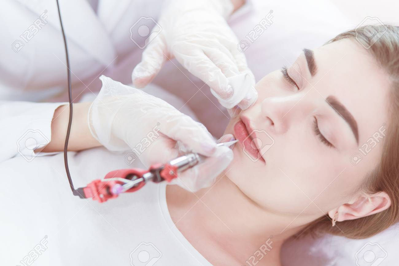 A young girl having red lips permanent makeup, micropigmentation - 122798289