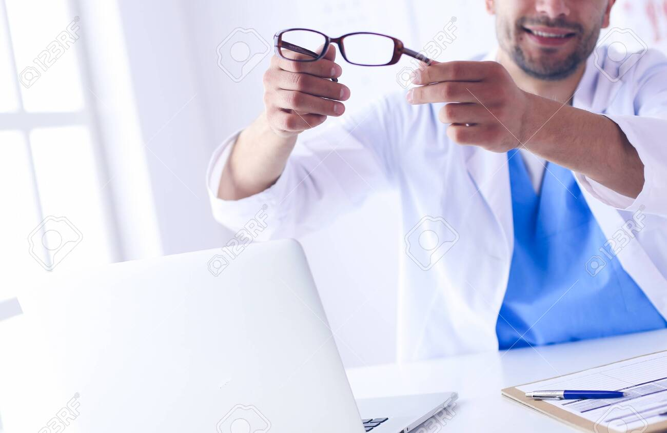 Portrait of a male doctor with laptop sitting at desk in medical office. - 137996837