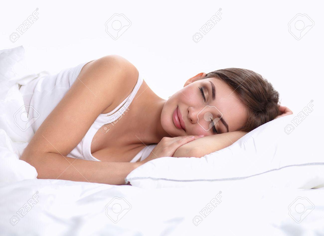 Mooi meisje slaapt in de slaapkamer liggend op bed geïsoleerde